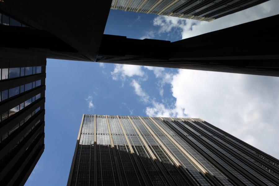 En klarblå himmel med besök av vita moln samverkar med skyskrapornas blanka glasfasader.