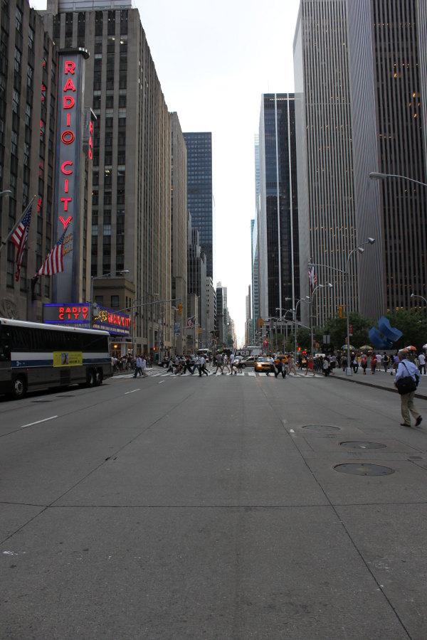 Sjätte avenyn, i höjd med Radio City Music Hall, vy söderut. Långt borta ses en buss som gör reklam för en tämligen trevlig musikal.