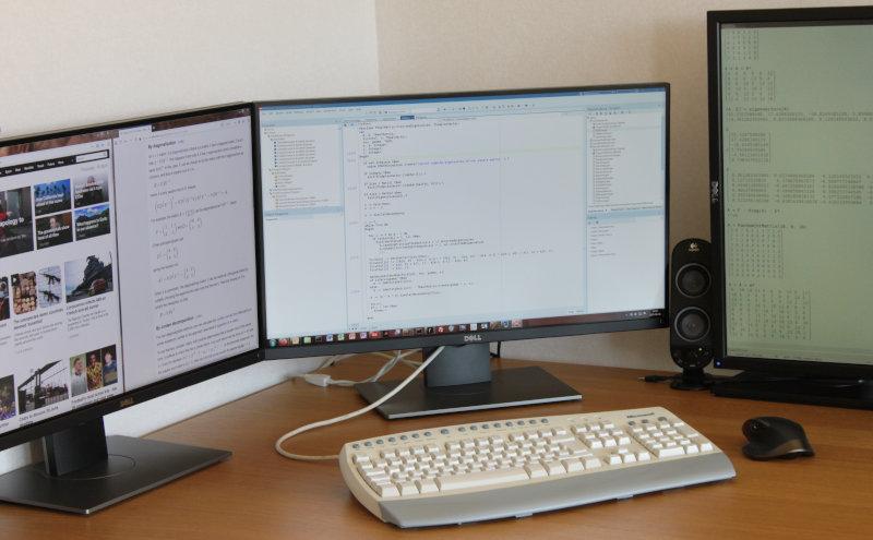 Ett hörnskrivbord med ett tangentbord av modellen Microsoft Internet Keyboard Pro, en mus av modellen Logitech MX Master, två nästan kantlösa 27-tumsskärmar i landskapsläge bredvid varandra, en 24-tumsskärm i porträttläge och den ena i ett par av högtalare. Tangentbordet är alldeles rent.
