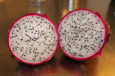 Öppen röd drakfrukt med vitt fruktkött, delad på mitten