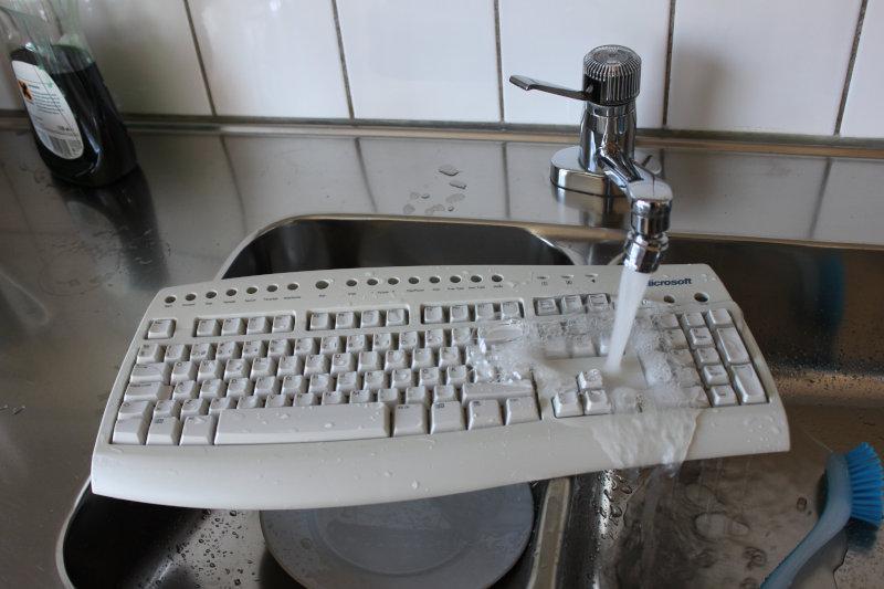 Ett tangentbord av modellen Microsoft Internet Keyboard Pro rengörs under rinnande vatten i en diskho i ett kök.