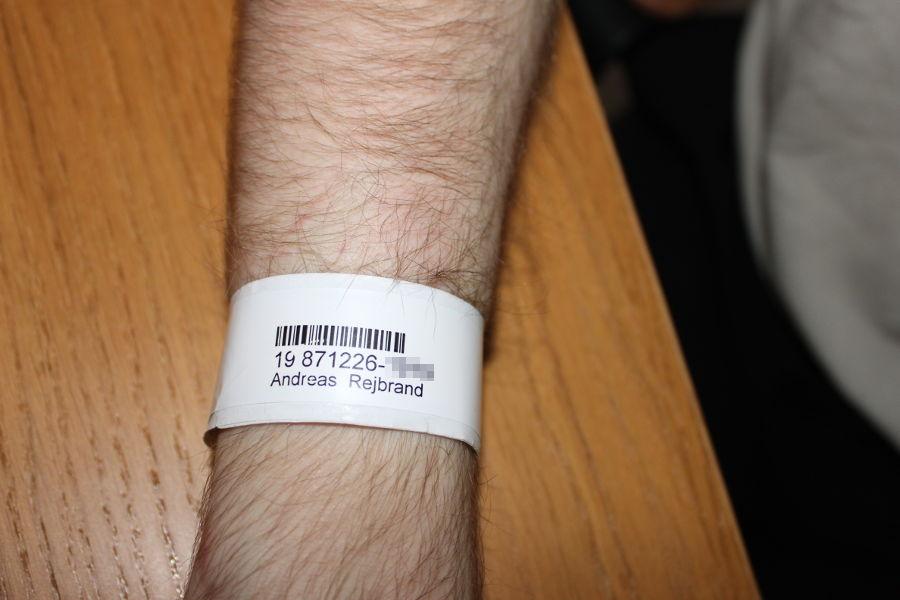 En arm med ett patientband kring handleden.